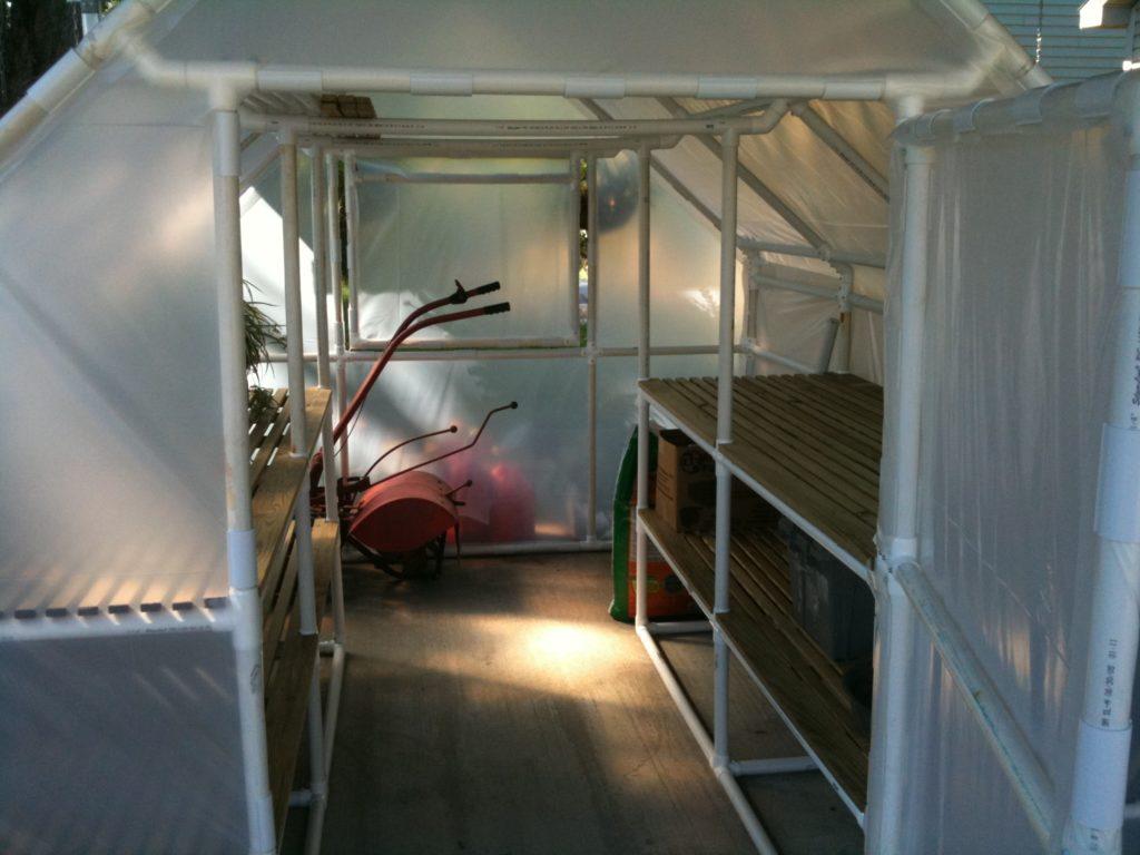 На фотографии показано, как выглядят стеллажи в теплице для выращивания овощей и фруктов